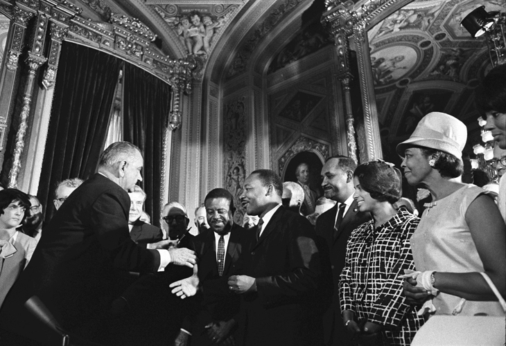 President Lyndon B. Johnson moves to shake hands with Martin Luther King  Jr. while others look on. August 6  1965 LBJ Library photo by Yoichi Okamoto